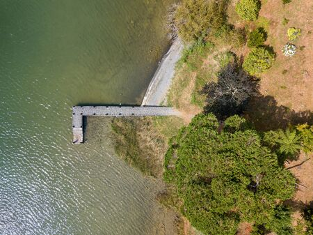 Aerial view of beautiful stone pier in Furnas lagoon, Azores islands. Drone landscape view with lines and textures. Top view of  romantic scenary, tourist attraction of Portugal.