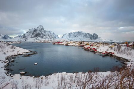 Beautiful village of Reine in Lofoten Islands, Norway. Snow covered winter landscape at sunset. Amazing tourist attraction in the polar circle. Panoramic view. 版權商用圖片 - 129589546