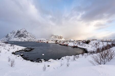 Beautiful village of Reine in Lofoten Islands, Norway. Snow covered winter landscape at sunset. Amazing tourist attraction in the polar circle. Panoramic view. 版權商用圖片 - 129589549
