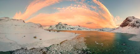 Aerial drone panorama photo. Beautiful sunset over the mountains and sea of the Lofoten Islands. Reine, Norway. Winter landscape with amazing colors. 版權商用圖片