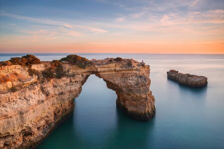 Algarve beach, romantic couple watching the sunset. Loving moment under natural arch carved in stone is a tourist attraction of the south coast of Portugal. Panoramic view from the cliff. 版權商用圖片 - 131339607