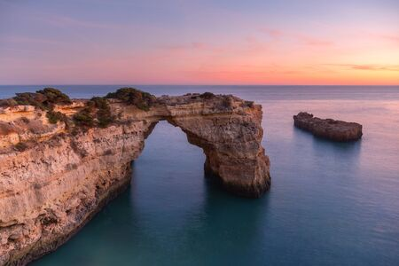 Algarve beach at sunset. Loving moment under natural arch carved in stone is a tourist attraction of the south coast of Portugal. Panoramic view from the cliff.