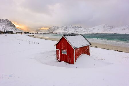 Lofoten Islands in Norway and their beautiful winter scenery at sunset. Idyllic landscape with red house on snow covered beach. Tourist attraction in the arctic circle.