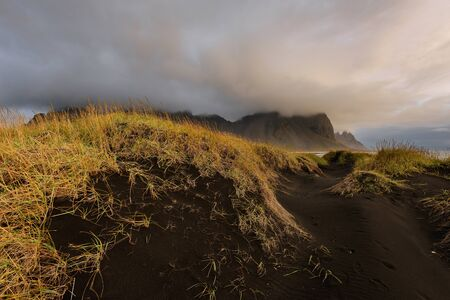 Magical landscape of Vestrahorn Mountains and Black sand dunes in Iceland at sunrise.  Panoramic view of the Stokksnes headland in a Colorfulseascape.
