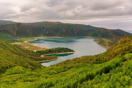 Panoramic view of natural landscape in the Azores, wonderful island of Portugal. Beautiful lagoons in volcanic craters and green fields. Tourist attraction and travel destination.