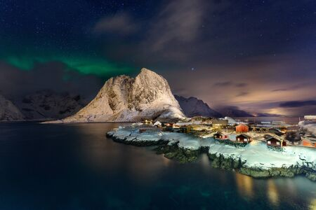 Beautiful Northern Lights in Hamnoy, Lofoten Island in Norway. Aurora Boreal over the small fishing village with its traditional red huts. Majestic green night sky.