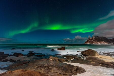 Beautiful Northern Lights in Lofoten Island in Norway. Aurora Borealis over the beach. Majestic green night sky.