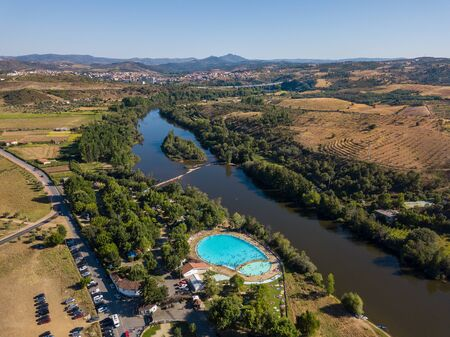 Happy people swimming on vacation. Aerial view over amazing pool. Drone point of view in summer landscape. Swimming pool in Mirandela, Portugal.