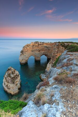 Algarve in Portugal and its amazing beaches, is a summer holiday destination for many tourists in Europe. Landscape with cliffs on the coast at colorful sunset. Pure nature, blue sea, sand.