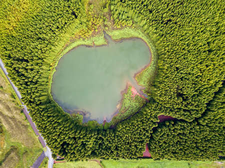 Ghost shaped drone landscape. Top down aerial view of a small pond in the middle of a forest, reflecting clouds in the sky. Bird view of Canary lagoon in Azores, Portugal.