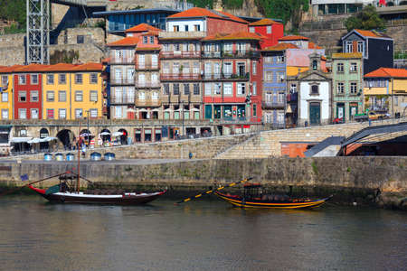 Porto, Portugal panoramic cityscape on the Douro River at sunset. Urban landscape at sunset with traditional boats of Oporto city. Downtown and historic center, travel destination. Oporto landmark.