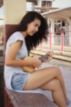 acoustical: Blur Woman playing ukulele, vintage style.
