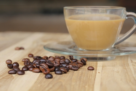 coffeetree: Cup of coffee and coffee beans on wooden background. Stock Photo