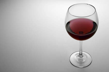 white wine: Glass of Red Wine 2. Glass containing red wine. Backlit white gradient background with Copy Space at the left.