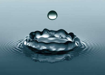 disrupting: Making an Impact. Close-up of water droplets splashing into a calm body of water. Stock Photo