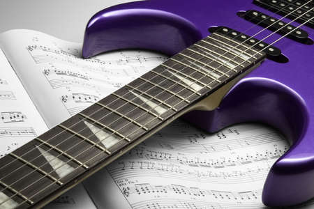 Electric Guitar on Sheet Music. A purple electric guitar on top of an open sheet music book.