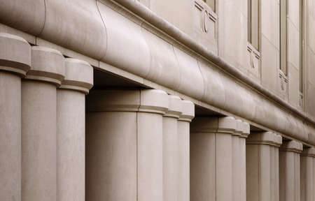 Building with Columns. Architectural details of a large city bank. Focusing on the front of the building, the pillars, and the first floor windows.