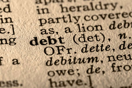 pronounce: The word debt. Close-up of the word debt in a dictionary.