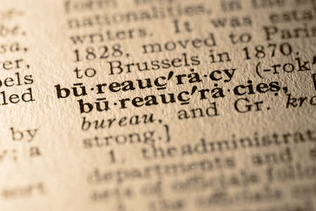 pronounce: The word bureaucracy. Close-up of the word bureaucracy in a dictionary.