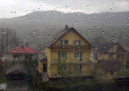 Rain drops on window through a house located in small country side town named Limanowa located in South Poland, Europe