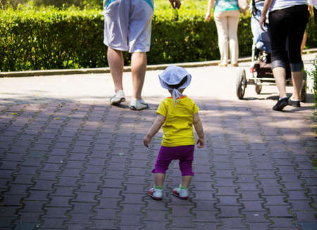 A kid in yellow t shirt follow parents in a park in summer 版權商用圖片