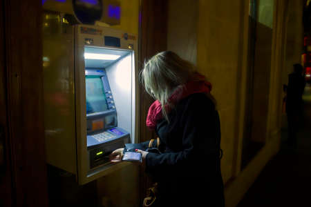 Krakow, Poland - October 25, 2014: A woman using ATM at night in winter Éditoriale