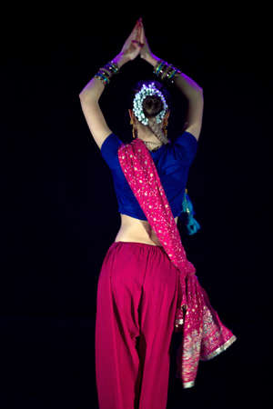 Krakow, Poland - March 22, 2015: A female dressed up Indian traditional cloths performing classical dance on stage