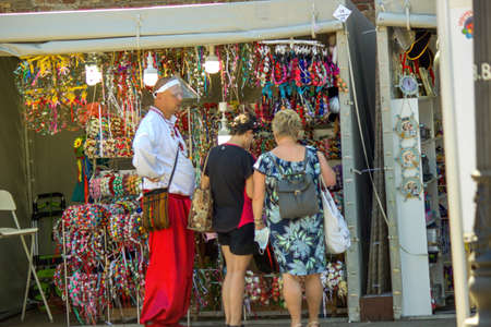 Gdansk, North Poland - August 15, 2020: A man in polish traditional wear making living by selling souvenir wearing protection mask during covid 19