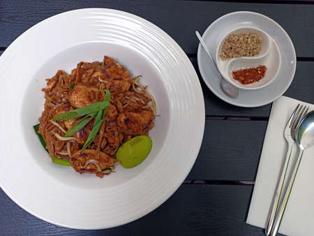 Pad thai , Stir fried dish made with noodles, chicken, vegetables, peanuts and slice of lemon on a plate against wooden pattern background and fork utensils. Reklamní fotografie
