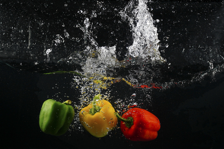 several coloured paprika falling into water splash with many bubble