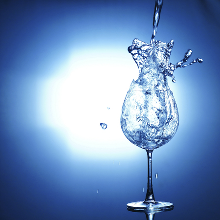 Pouring water into glass with splashed out