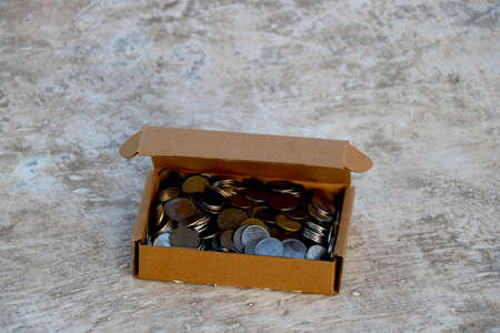 stack of Indian coins in brown paper box