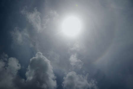 Dramatic sky bright sun behind cloud in blue sky