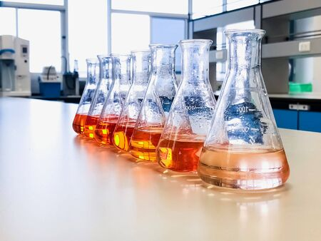 The Erlenmeyer flasks on Bench Laboratory prepare for waste water experiment with colorful indicator chemical and solvent solution. Calibration curve analysis of iron show the gradient orange color.
