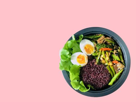 STIR FRIED CHINESE KALE WITH CANNED FISH taste spicy with chili cooked in the black metal pan eat with egg boiled salad and rice-berry isolated in pink background has copy space and clipping path. Imagens