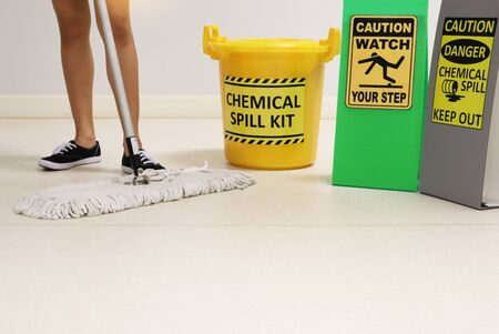Janitor cleaning floor in medical service room or laboratory with caution tag sign watch your step and chemical spill out beside chemical spill kit yellow bucket for response chemical spill out cases.