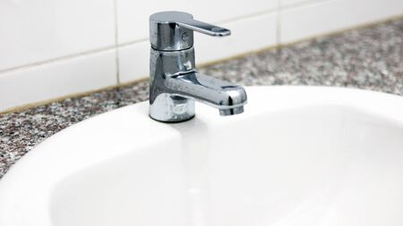 The Silver Faucet with white ceramic sink in the bathroom, using for cleaning and washing hands, hygiene health care for protecting corona virus. Remove and kill bacteria fungal by keeping sanitation.