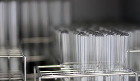 Transparent clear test tubes on racks, clean glasswares on the laboratory shelf for measuring solution or solvent in science experiment, chemistry equipment tools for analysis sample. Selective focus. Archivio Fotografico