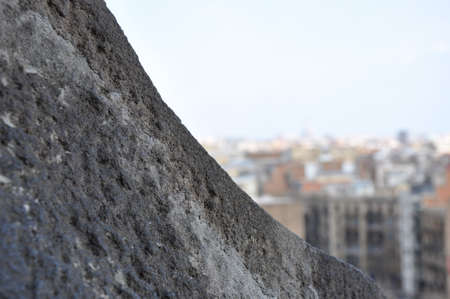 Extreme close up of stone structure worn by the elements and overlooking a metropolitan city