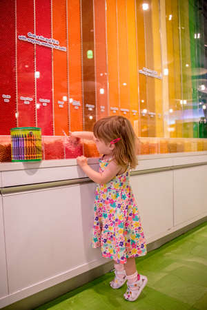 Little girl standing on tiptoe in a colorful art supply store selecting colored wax crayons from a display with wall stripes in an extensive range of colors and hues in the spectrum Editorial