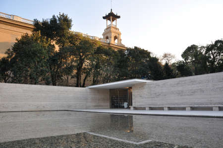 German Pavilion in Barcelona with large reflecting pool and trees lined up around marble walls Redakční