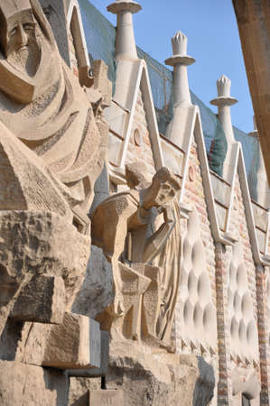 Architectural detail of the Sagrada Familia, Barcelona Spain designed by Antoni Gaudi showing a seated figure of a man on the exterior facade