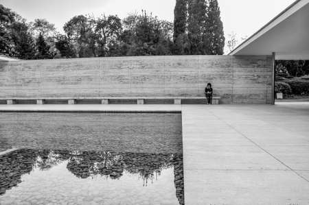 Single person sitting on bench at German Pavilion with calm reflecting pool in foreground
