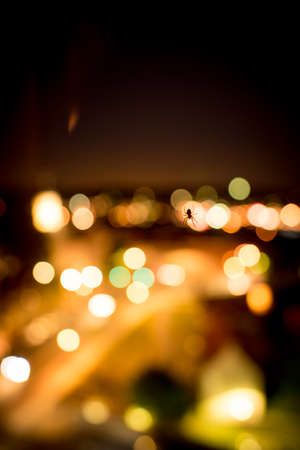 Spider backlit by a colorful glow and bokeh of city lights shining in the darkness viewed as a silhouette 스톡 콘텐츠