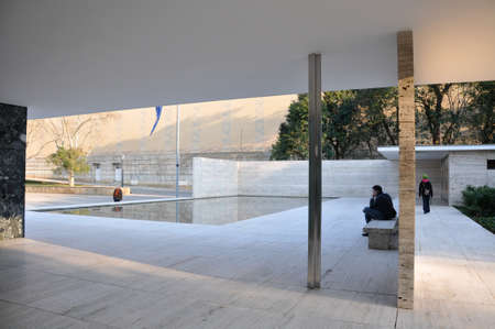 ludwig: Reflecting pool in geometric building with man seated on stone bench nearby as woman walks towards exit in Barcelona Pavilion by Ludwig Mies van der Rohe Editorial