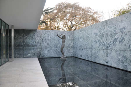 Attractive geometric patio with female statue at one corner and a shallow reflecting pool in Barcelona Pavilion by Ludwig Mies van der Rohe