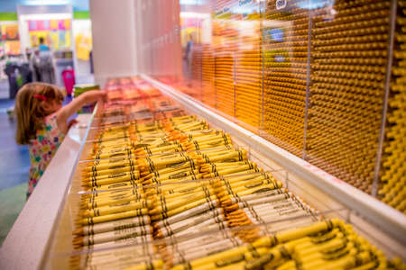 Cute little girl selecting art supplies in a store reaching up to choose colorful wax crayons from the display