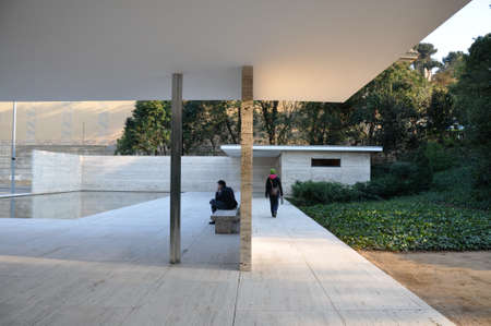 ludwig: Man contemplates as he sits in patio by reflecting pool as woman leaves via corridor behind him in Barcelona Pavilion by Ludwig Mies van der Rohe