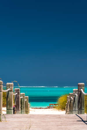 Steps with rustic wooden poles leading down to an azure blue ocean on a tropical beach on the Turks and Caicos Islands in the Caribbean for a perfect summer vacation