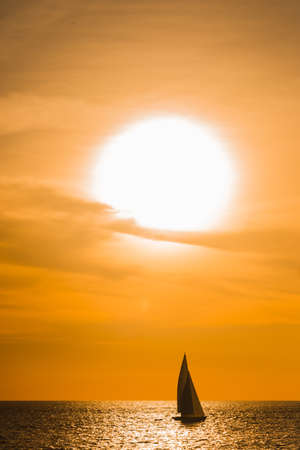 Sailboat sailing on the ocean during a spectacular orange tropical sunset silhouetted against the vivid sky in a reflected path of sunlight on the water Reklamní fotografie